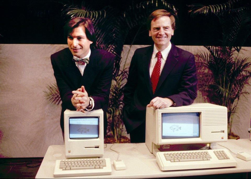 Steve Jobs e John Sculley apresentando o novo Macintosh desktop computer em janeiro de 1984, num evento com acionistas em Cupertino, California. Conflitos frequentes com John Sculley (ex-CEO da Pepsico), levaram o Presidente escolhido pelo próprio Steve Jobs a pedir a demissão de Jobs ao Conselho em 1985. Imagem: Business Insider